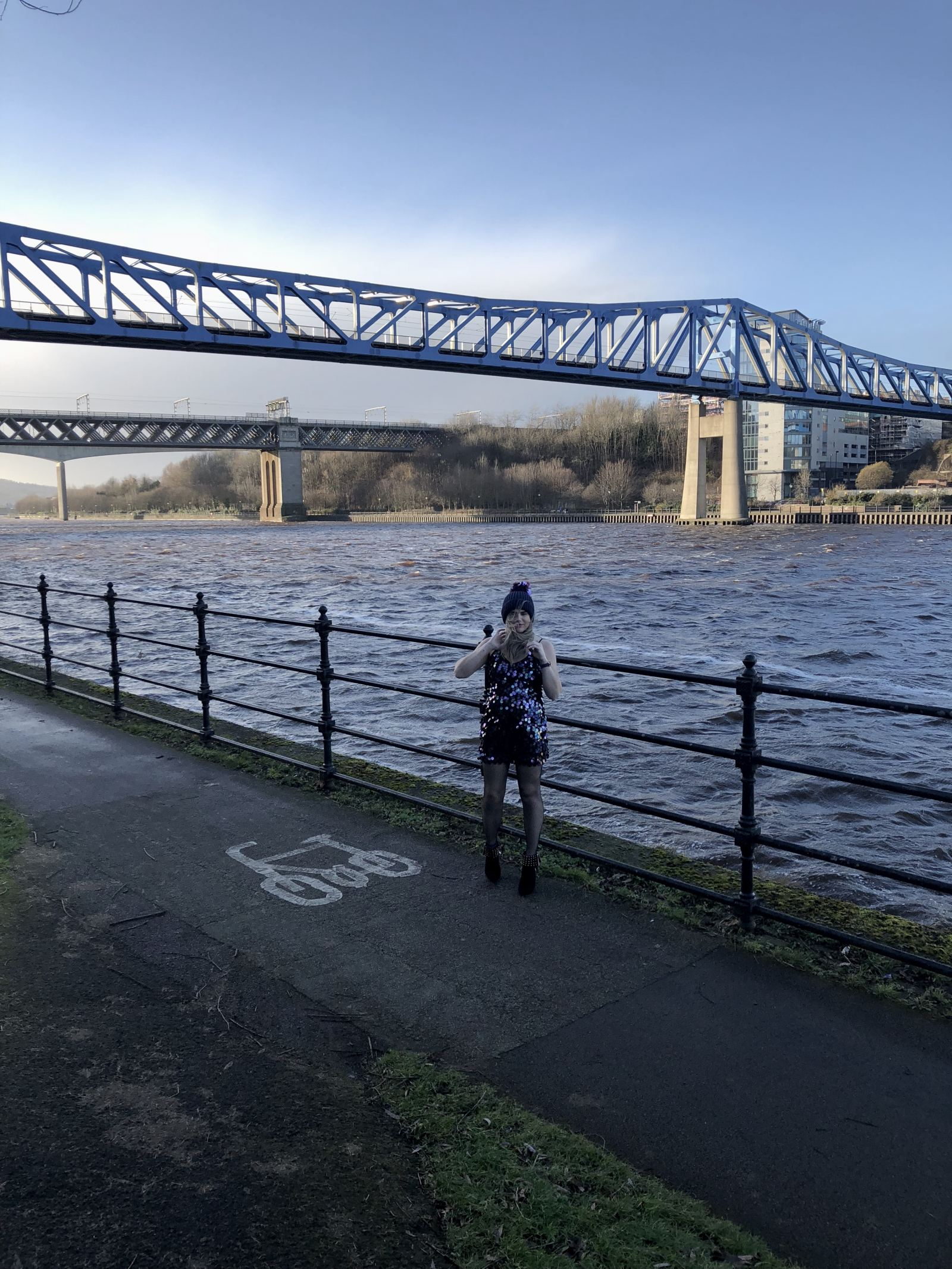A picture of Pixie Tenenbaum on the Gateshead Quays wearing a 90's style slipdress covered in paillettes, studded boots and a bobble hat with the wind blowing her hair. Fashion Voyeur Blog