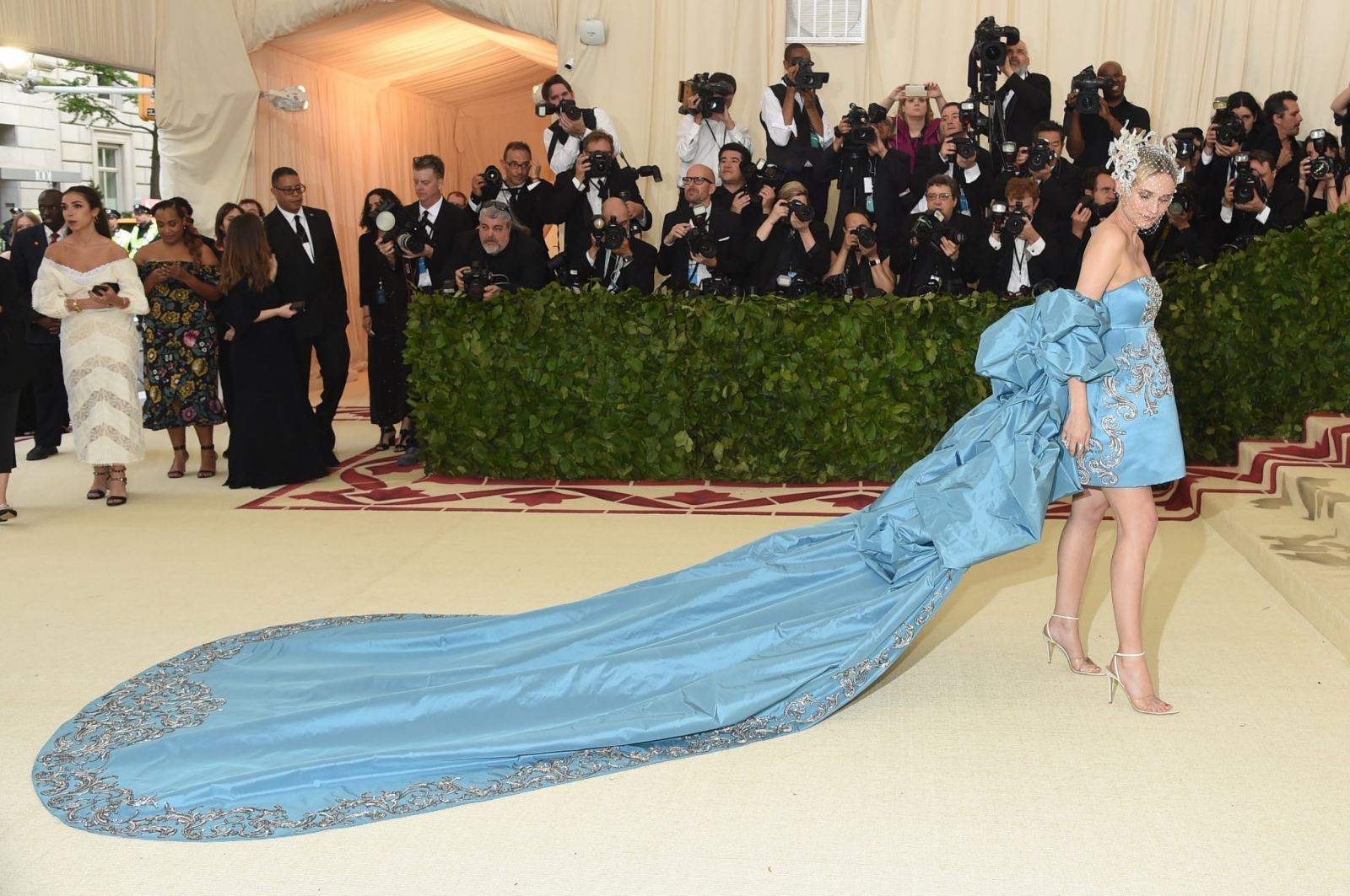 An image of Diane Kruger wearing a pale blue bandeau mini dress with ruched full length cape and train at the 2018 met gala
