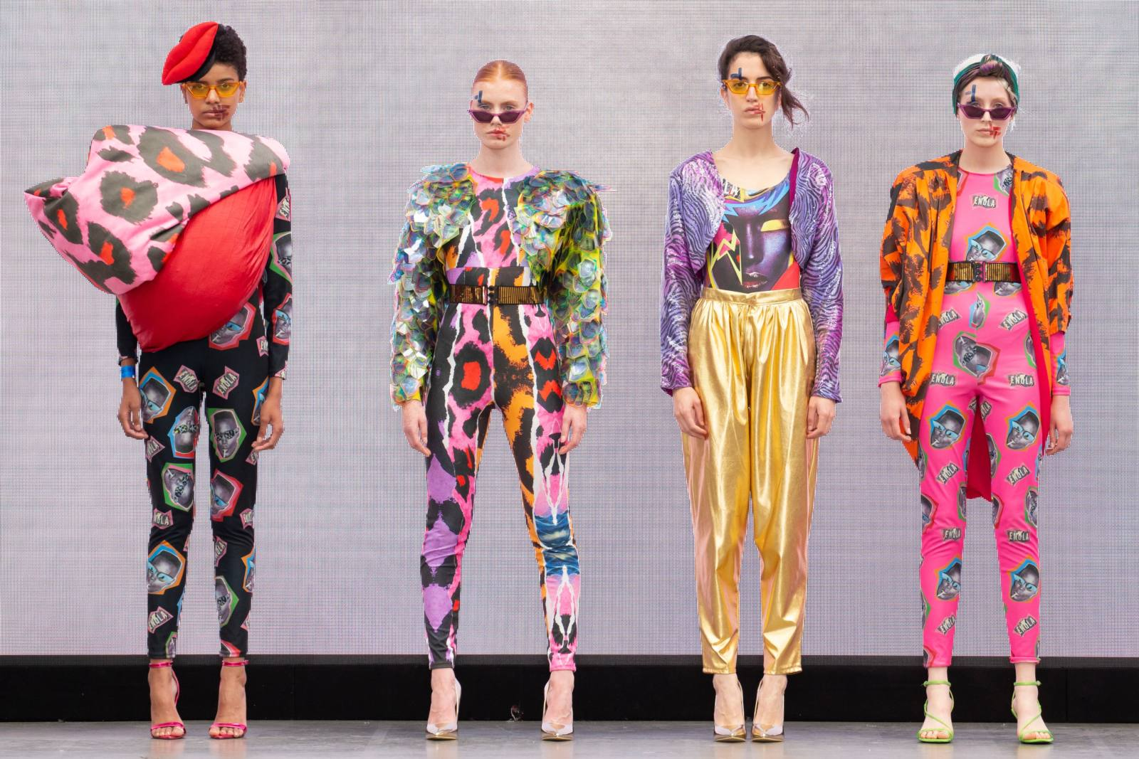 A group of models on the runway for the Liverpool John Moores University Graduate Fashion Week 2019 runway show wearing brightly coloured clothes 1980's style