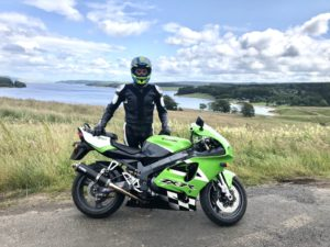 An image of Bo at Kielder Reservoir on his 40th birthday in full leathers next to his Kawasaki ZX7R on a sunny day
