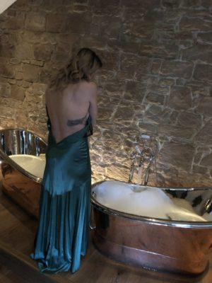 Pixie Tenenbaum standing in front of two filled copper slipper tubs at Beadnell Towers Hotel in the Muckle Hoose Suite
