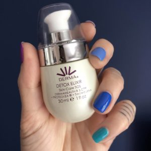 A close up image of Pixie Tenenbaum's hand holding a bottle of Viv Derma's Skin Elixir, a skin hero product for calming skin deemed to be in crisis