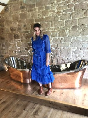 Pixie Tenenbaum stands in front of twin copper slipper tubs wearing a blue midi prairie dress and brown cowboy boots at Beadnell Towers Hotel