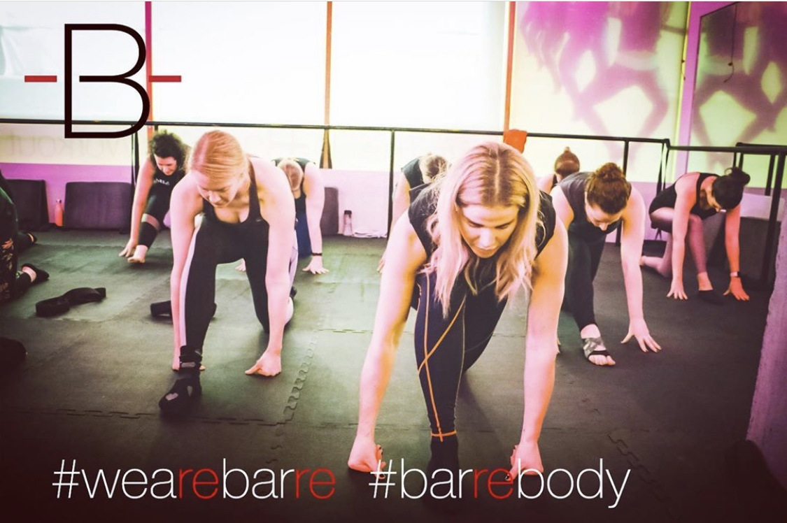 An image taken from the Barre Body Campaign shot by Jason Holcomb for The Barre Workout Newcastle featuring Pixie Tenenbaum and other clients of The Barre taking a 2nd Barre class and being photographed in a forward facing Split Stretch position in the large fitness studio